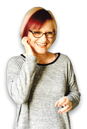 A picture of Susan Lockwood who has glasses and a purple stripe in her hair, laughing