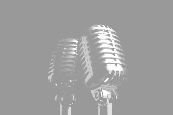 Black and white photo of 1950's style microphones on black background